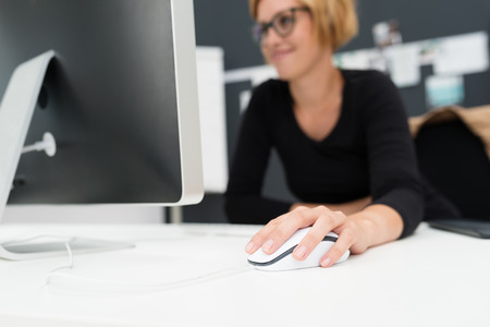 Businesswoman using a wired computer mouse to navigate as she works on her desktop computer, focus to the mouse