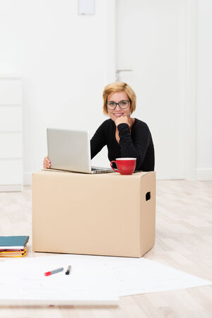 moving office: Businesswoman working from home in a new build house sitting on the floor with her laptop balanced on a cardboard packing carton surrounded by large sheets of paper and her coffee Stock Photo