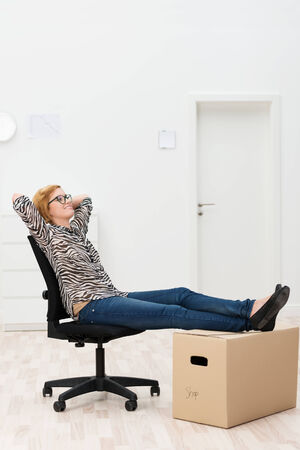 empty: Woman relaxing in her new home or office sitting in an office chair with her feet up on a cardboard packing carton Stock Photo