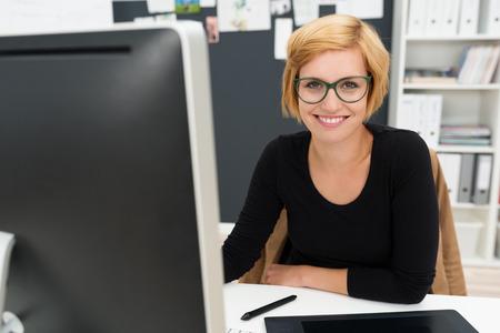 Bienvenus jolie jeune femme d'affaires assis à son bureau dans le bureau en souriant à la caméra son écran d'ordinateur