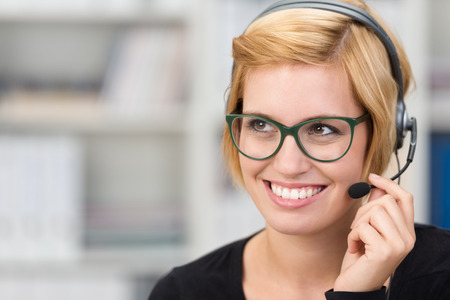 support agent: Attractive woman call centre operator wearing heavy framed glasses and a headset smiling as she listens to a conversation with a customer