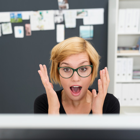 reacting: Young businesswoman reacting in surprise and shock to something on her computer monitor raising her hands in the air in open-mouthed amazement Stock Photo