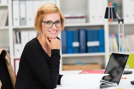 Sourire jeune femme d'affaires portant des lunettes assis à son bureau dans le bureau faire de la paperasse et en se tournant vers la caméra avec un sourire amical