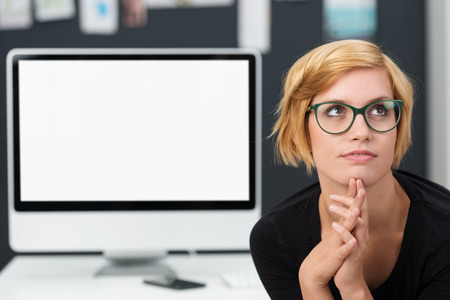 computer programmer: Young businesswoman trying to solve a problem sitting with clasped hands staring thoughtfully into the air in front of a blank desktop monitor with copyspace
