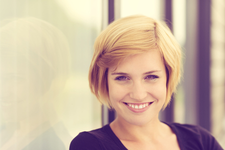 city living: Retro effect portrait of a smiling young woman with short blond hair standing alongside an angled wall with copyspace