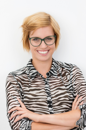 black rimmed: Smiling happy confident young blond woman wearing black rimmed glasses standing with folded arms grinning at the camera