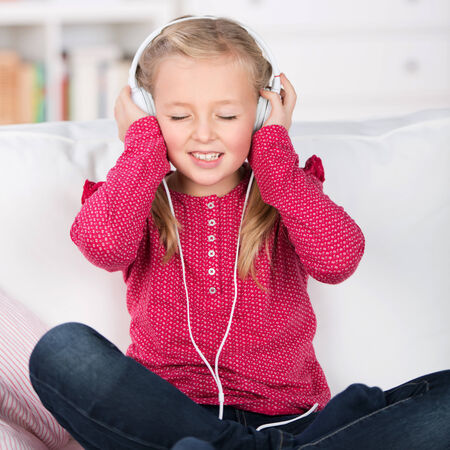 portrait of a female kid enjoying music with closed eyes photo