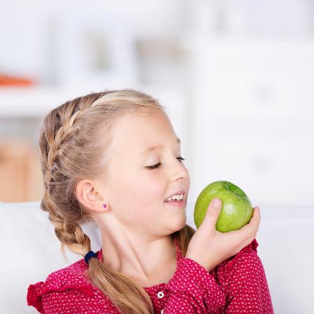 kids eating healthy: blond schoolgirl looking at green fresh apple Stock Photo