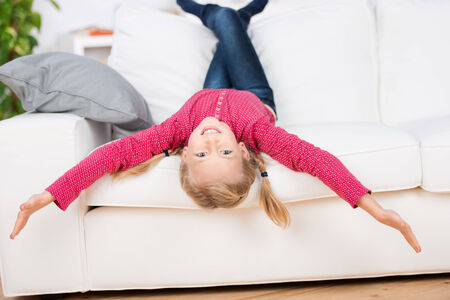moving down: Portrait of a playful girl lying upside down on sofa in the living room