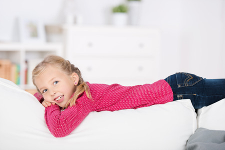Side view of a little girl lying on sofa at home photo
