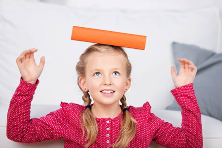 one room school house: closeup of a cute little girl balancing book on head at home Stock Photo