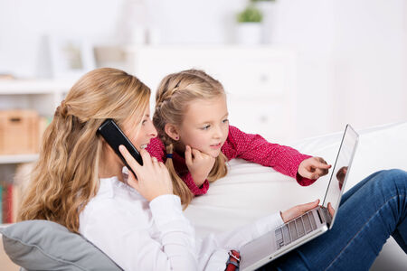 Mother and daughter using laptop and phone in the house