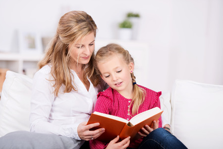 Mother and young daughter reading book on couch at home photo