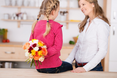 Little girl holding flowers behind her back by her mother on mothers day at home photo