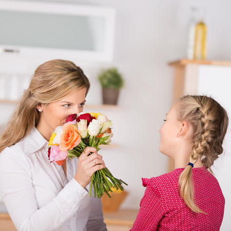 girl giving flowers to mother on her birthday Stock Photo