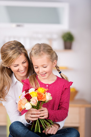 Little girl giving flowers to her mother on mothers day at home photo
