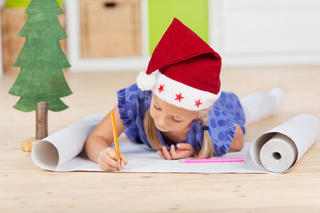 writing letter: Cute girl with christmas hat writing letter to santa