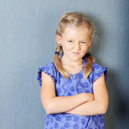 Portrait of little girl with arms crossed grimacing while standing against blue wall
