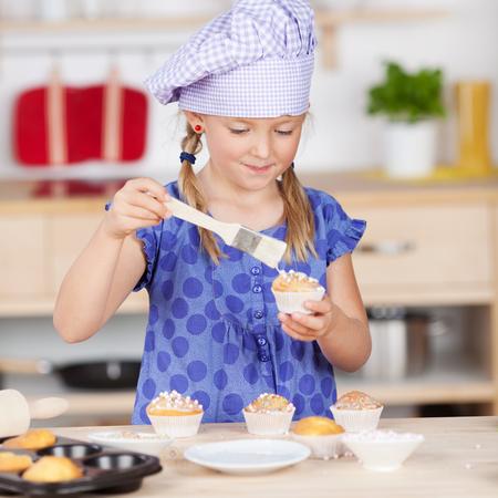 garnishing: Cute little girl garnishing cupcakes at kitchen counter