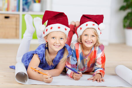 Portrait of happy girls in Santa hats drawing on chart paper while lying on floor at home photo