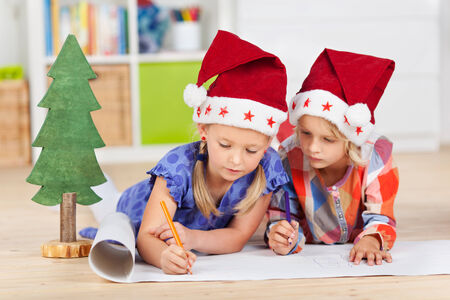 Two kids with santa hats writing wishlist while lying on the floor photo