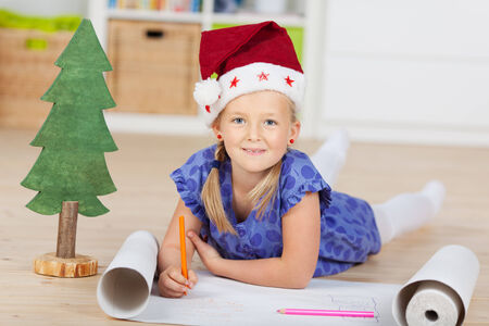 laying little: Portrait of cute girl in Santa hat drawing on chart paper at home Stock Photo