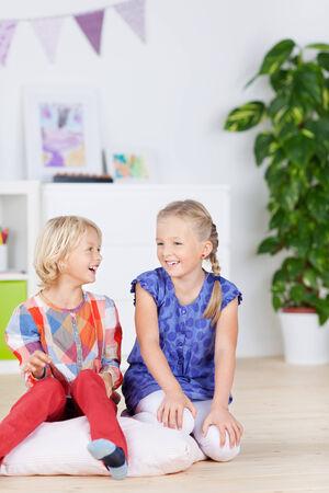 Happy little girls smiling together on hardwood floor at home photo