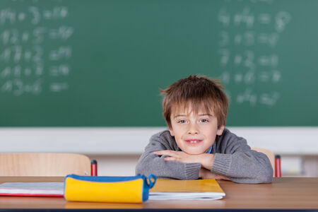 sums: Young boy sitting and leaning over the desk in the classroom supporting his chin on the hands with the blackboard in the background