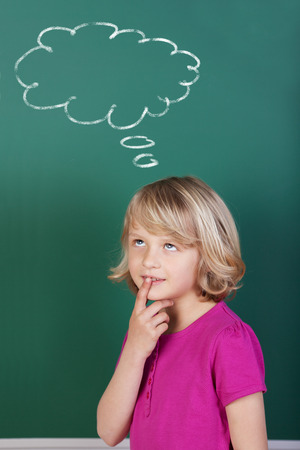 child looking up: Young blond schoolgirl thinking with a thinking comic strip balloon drawn in the blackboard