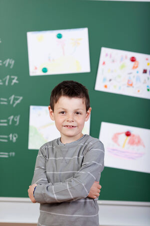 sums: Schoolboy posing with arms crossed in front of blackboard Stock Photo