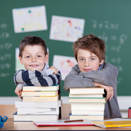 Two little boys with a stock of books inside the classroom photo