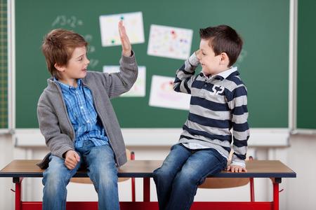 manos aplaudiendo: Dos estudiantes varones jóvenes entre sí dando un alto cinco en el aula Foto de archivo