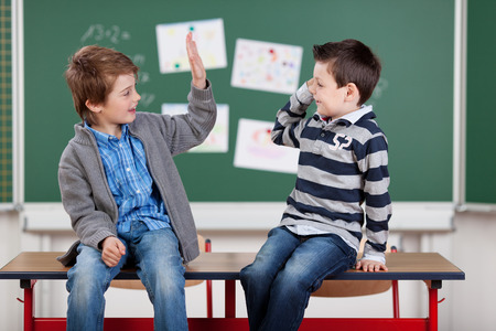 Two young male students giving each other a high five in the classroom