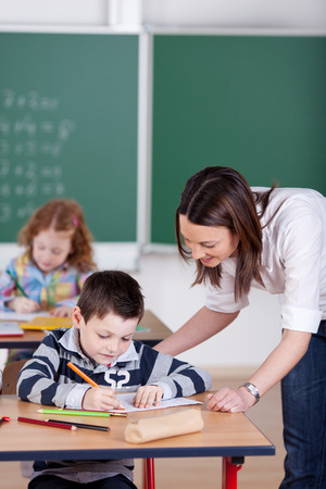Teacher helping student one on one at the classroom photo