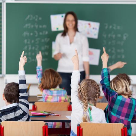 school teachers: Retrato de los ni�os levantaron la mano en el aula Foto de archivo