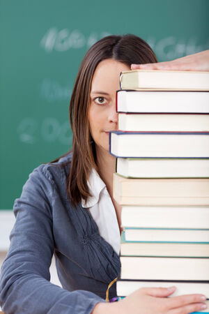 Portrait of teacher behind a pile of books at the table photo