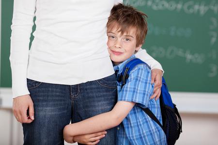 mama e hijo: Retrato de los escolares amoroso abraza a su madre después de la escuela