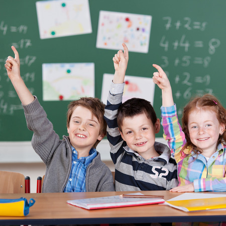 Three schoolchildren raising their hands in front of the blackboard