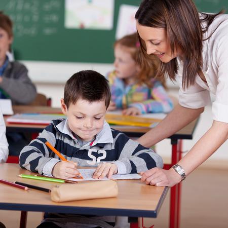 Učitel pomáhá elementární student v učebně