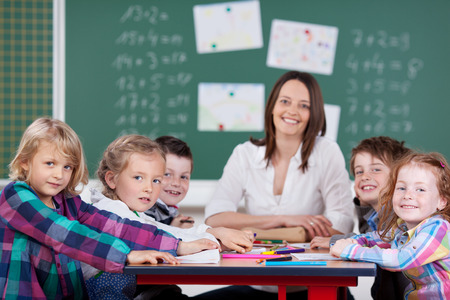 all smiles: Female teacher leading a class activity with a group of her young schoolchildren all seated together around a table as she smiles happily at the camera with a chalkboard background