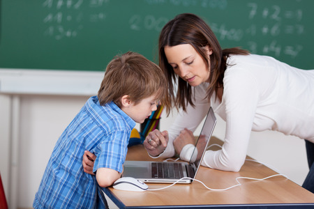 Teacher teaching elementary student from laptop in the classroom photo