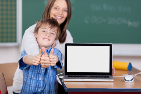 Portrait of teacher and student showing their thumbs up in the classroom photo