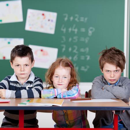 desorden: Tres niños que se sientan molestos en el aula