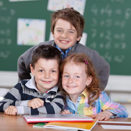 niños en la escuela: Niños sonrientes que tienen un trabajo de grupo en el aula