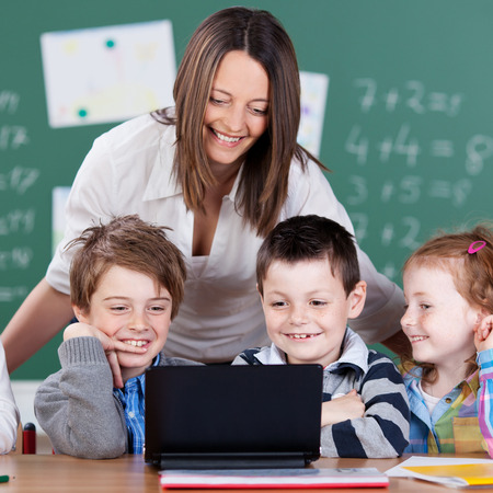 Portrait of pupils and teacher looking at digital tablet in the classroom