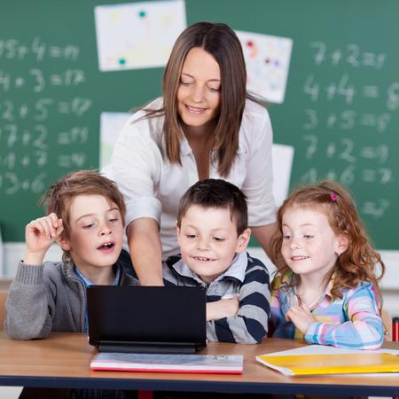 salon de clases: Retrato de los niños y maestro mirando el ordenador portátil en el aula Foto de archivo