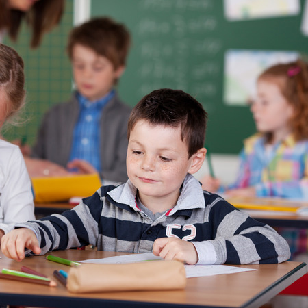school age boy: Concentrated school children being occupied in art class Stock Photo