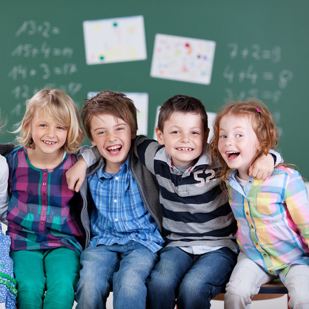 during: Portrait of happy little students during the break time in school Stock Photo