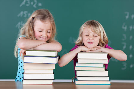 shut: Two playful attractive young blond girls with their school books stacked high on a desk in the classroom leaning on them with their eyes closed and big smiles Stock Photo