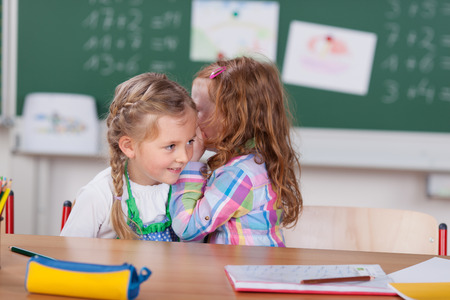 Little girl whispering to her beautiful young friend in class at school telling her a great secret or gossiping about a classmate, chalkboard and notices background Stok Fotoğraf